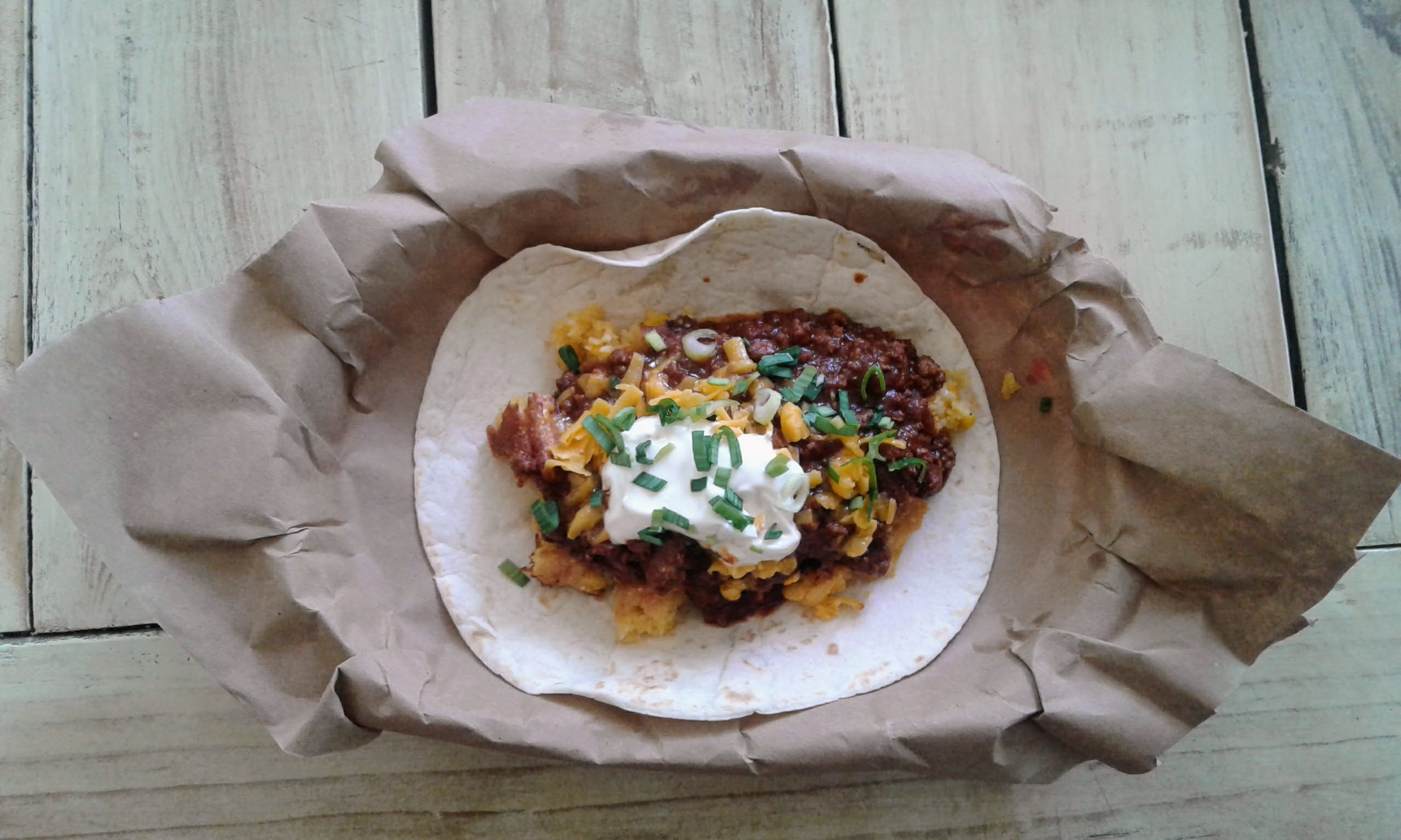 The Texan Taco with Chili, Jalapeno Cheese Corn Bread, Cheddar Cheese, Sour Cream and Green Onions