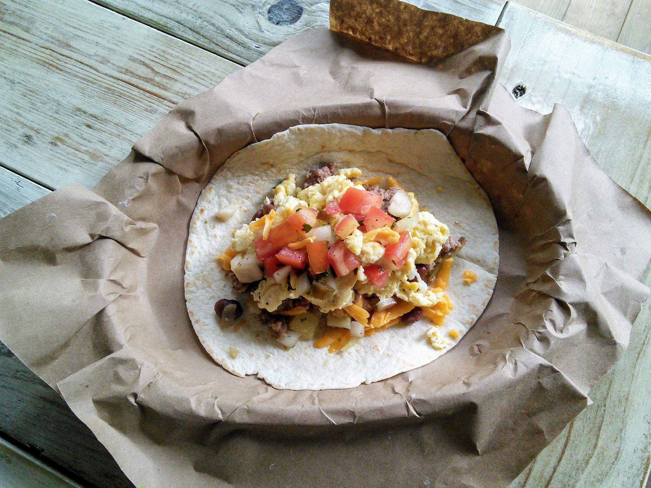 The Boss Taco with Ground Beef, Charro Beans, Potato Hash, Eggs, Cheddar Cheese and Pico de Gallo